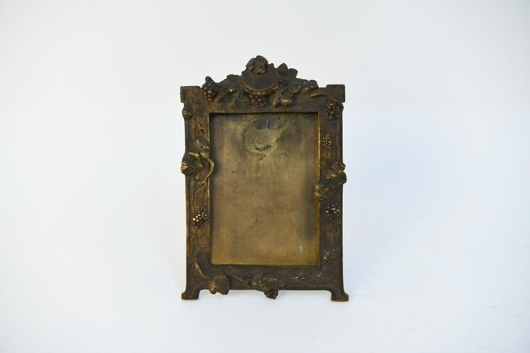 A fine, Art Nouveau cast bronze standing frame with grape fruit and foliage with central crest at top. The original patina will bring you back to the turn of the century. Signed, A. Marionenet (French, 1852-1910), will fit an H 6.25