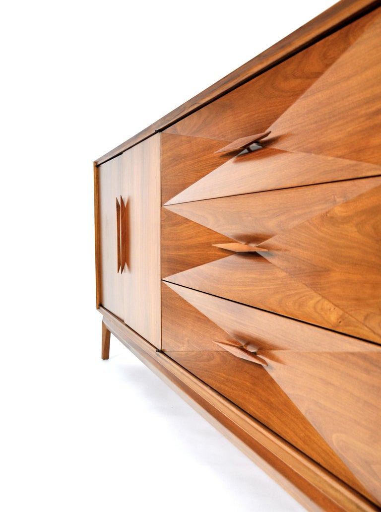 A superb midcentury modern walnut credenza by Albert Parvin. Freshly restored and ready for your home or office, the sculptural dresser provides ample storage space. The drawer fronts have a striking concave diamond front design and signature