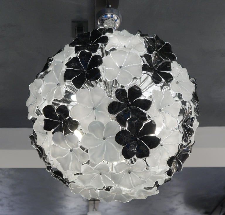 Exclusive flowers chandelier in Murano blown glass, black and white colour Entirely worked by hand with extreme care and precision. Work performed by Alberto Donà in 1994.  The chandelier contains 81 elements of flowers in Murano glass and six