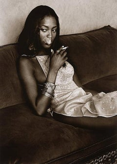 Naomi Campbell - the supermodel smoking while sitting on a sofa