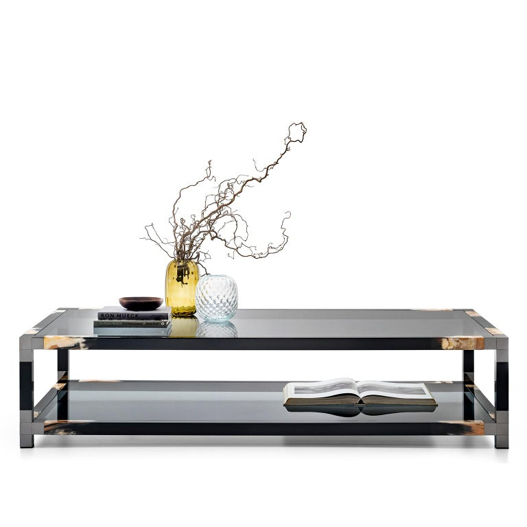 Effortlessly appealing and perfect in proportions, our Alcamo coffee table features an elegant tabletop and a lower shelf in tempered smoked glass. The rectangular structure in glossy black lacquered wood is adorned with gunmetal brass details and