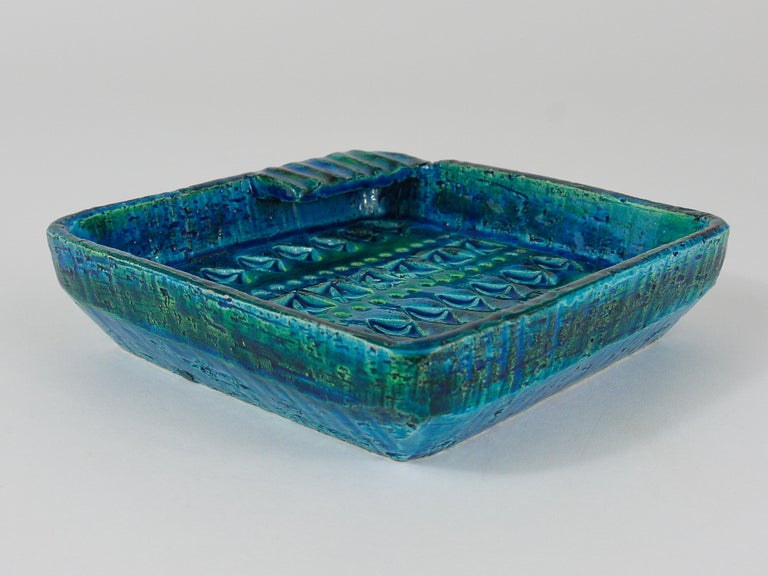 A beautiful, decorative midcentury Rimini blue glazed ashtray. Designed by Aldo Londi, manufactured by Bitossi Ceramiche / Italy in the 1950s. Handcrafted with hand carved geometric design in a glazed vibrant turquoise and cobalt blue. In very good