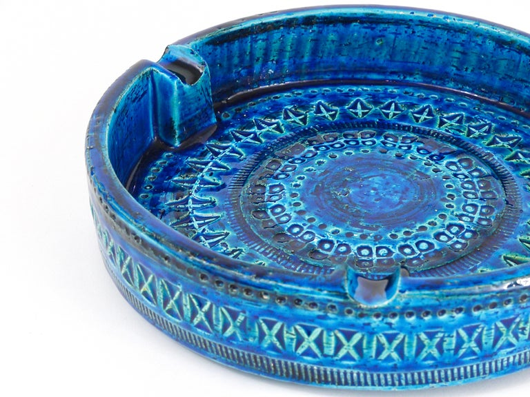 A beautiful, decorative midcentury Rimini blue glazed ashtray. Very large, has a diameter of 9 1/2 inches, Designed by Aldo Londi, manufactured by Bitossi Ceramiche / Italy in the 1950s. Handcrafted with hand carved geometric design in a glazed