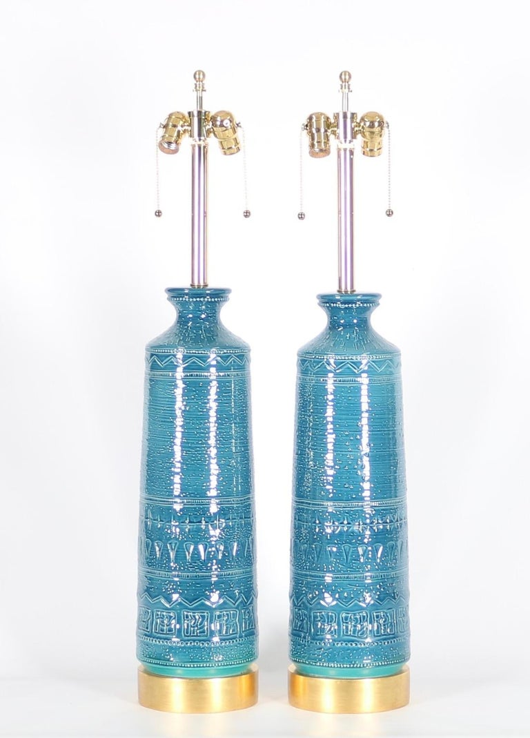 Hollywood Regency Bitossi style pair of table lamps in carved ceramic with blue & aqua glaze, mounted on gilt wooden bases. The pair was designed in the 1960s in Italy and is in great vintage condition with age-appropriate wear. Fully restored with