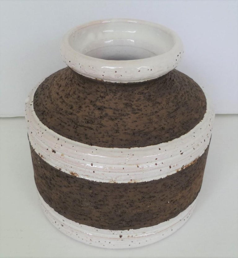 Striking Italian Mid-Century Modern vase by Aldo Londi for Bitossi and imported by Raymor in the 1960s. With a circular squat body, it has a a predominate rough textured cork like finish with circular divisions of white glaze around the body and