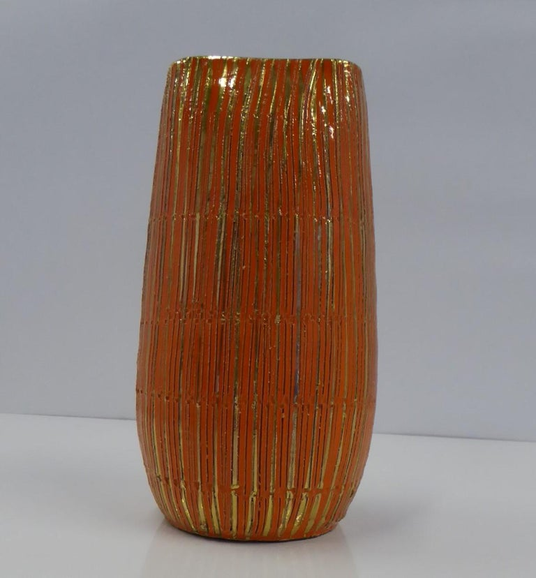 One of Aldo Londi's midcentury creations, his SETA (Silk) Series of Sgraffito Pottery for Bitossi in fun vibrant orange glaze and gold gilt. A lovely handmade striated vase with bands incised with small uneven shapes. The gold gilt stripes have been