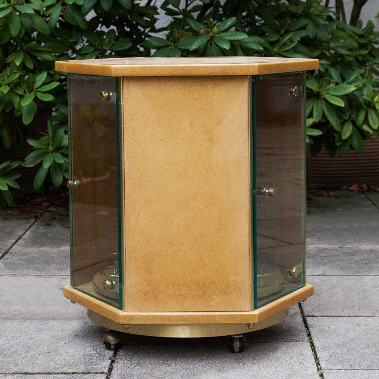Elegant Aldo Tura bar cart on brass rolls in hexagonal shape with three glass doors and a turnable bottle holder inside.  This particular bar cart was executed, circa 1970 and is in excellent condition. Along with artists like Piero Fornasetti and