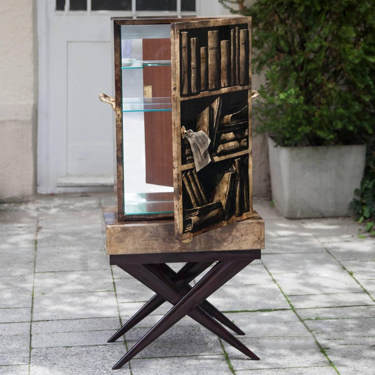 Wonderful sculptural bar cabinet made by Aldo Tura in the 1960s. The Trompe l'oeil painted goatskin surface seems in a three-dimensional book shelf based on a mahogany x base. Mirrored inside and fitted with an interior light. Dimensions: 122 H x