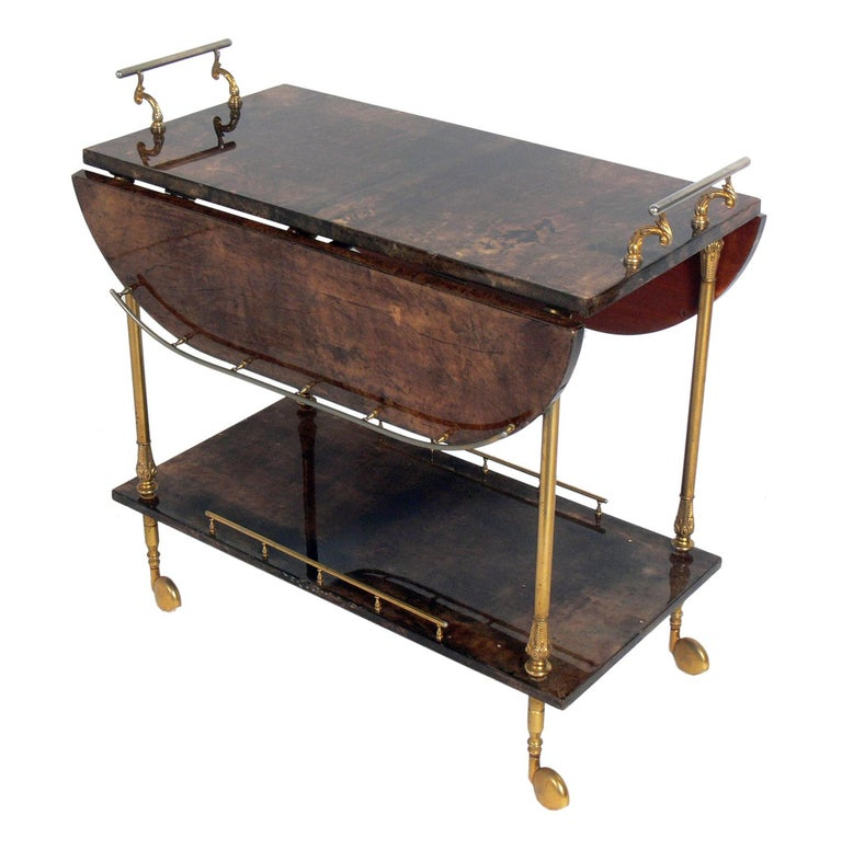 Aldo Tura Goatskin or parchment bar or tea cart, Italy, circa 1960s. Constructed of thickly lacquered goatskin or parchment and gilt metal hardware. Perfect bar or serving cart, or as rolling storage in an office.