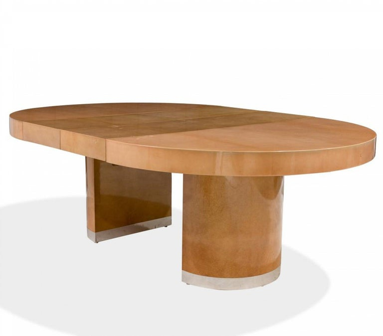 Italian midcentury circular goatskin center table with circular pedestal base with silver metal trim along base and an expandable tabletop with two leaves. (leaves: 16