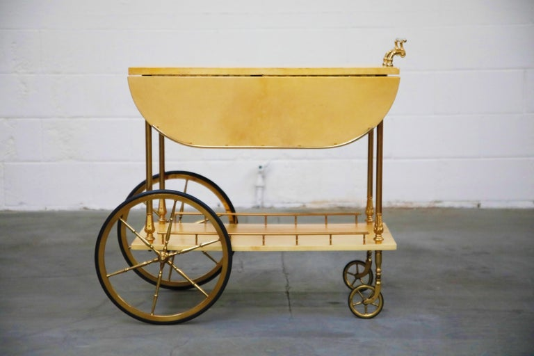 Beautiful bar cart by Italian artist-craftsman Aldo Tura, featuring the designers distinct use of brass and lacquered goatskin that Tura was well-known for. The quality of Aldo Tura's craftsmanship can be attributed to the fact that his work was