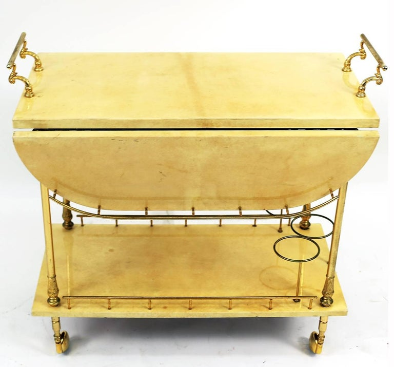 A beautiful ecru colored Aldo Tura lacquered goatskin two level bar cart trolley with drop down leaves and brass detailing. Excellent condition.   Overall dimensions of cart with drop leaves extended are 31 inches in length, 31 inches in depth and