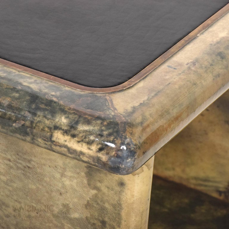Aldo Tura side tables made in patinated brass, lacquered goatskin and leather.   Goatskin displays multi colors ranging from light tan to dark gray. Table top covered in black leather with brass detail.  No stamp present from the maker.