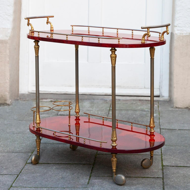 Wonderful bar cart made by Aldo Tura,Italy in the 1960s.  The bar cart was executed in lacquered red goatskin with brass applications and includes a bottle holder and it is in nearly excellent condition.  Along with artists like Piero Fornasetti