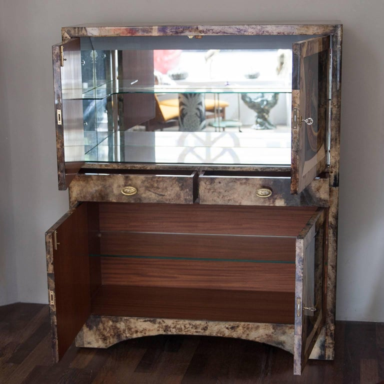 Wonderful sculptural bar cabinet made by Aldo Tura in the 1960s. The Trompe l'oeil painted goatskin surface seems in a three-dimensional classical dinner plate shelf. Mirrored inside and fitted with an interior light.