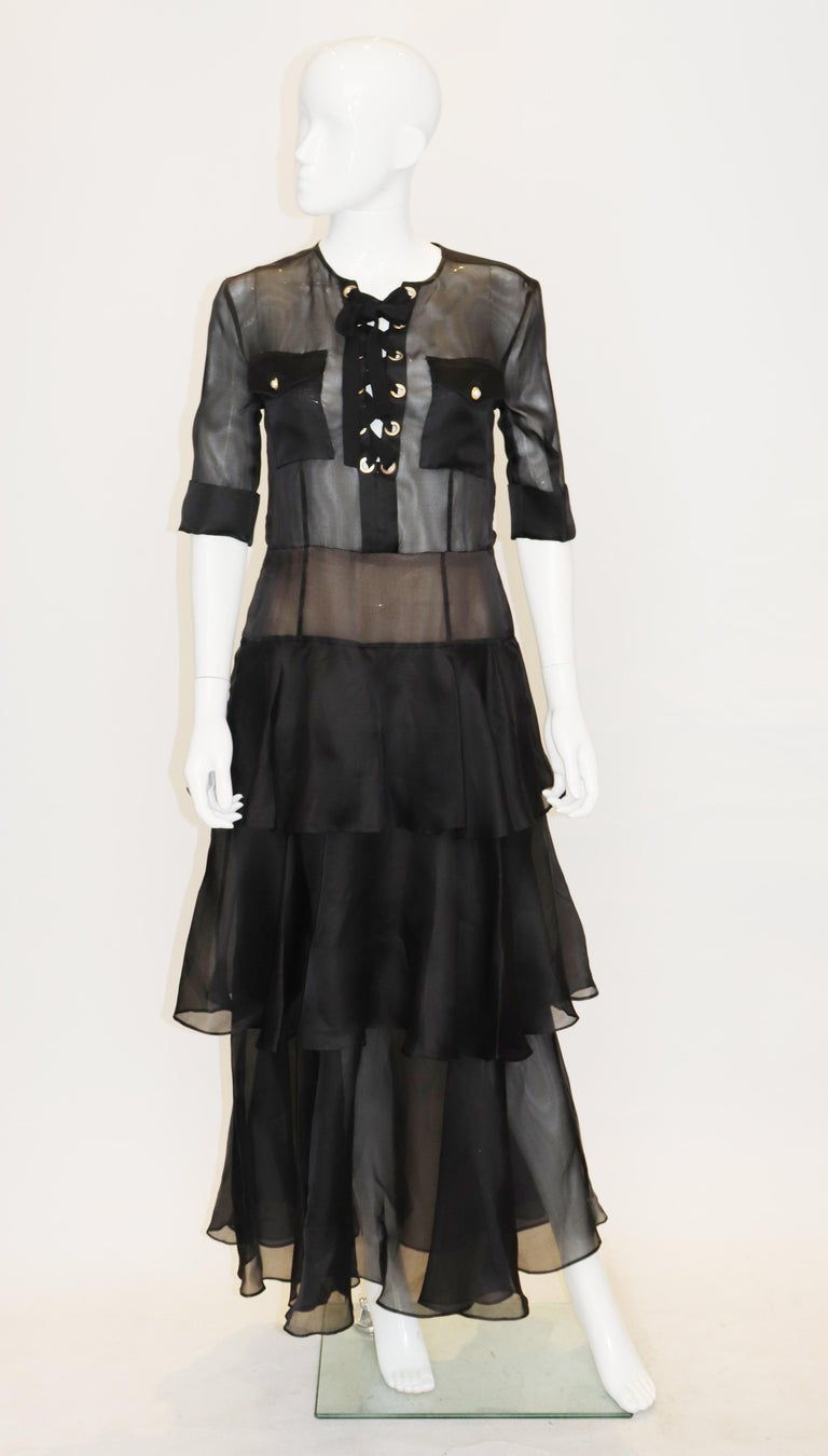 A head turning and chic gown in black silk by Alessandra Rich. The gown is collarless and has two breast pockets , short sleeves with turn up cuffs and a central back zip. It has a tiered skirt.