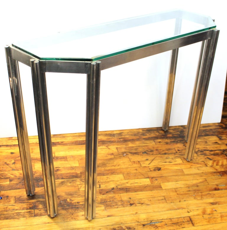Alessandro Albrizzi Mid-Century Modern console table in chrome and glass. The piece features six legs made up of octagonal bars. The frame is loosely articulated. Wear includes patina to metal appropriate to age and use and a larger chip to the