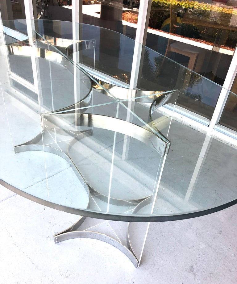 A racetrack dining table by Albrizzi. The base is Lucite with chrome metal. Glass top.