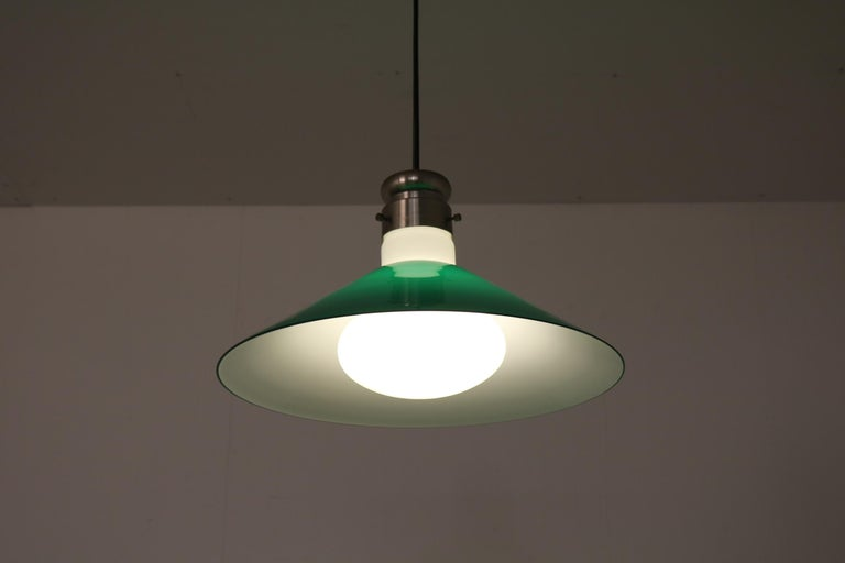 A beautiful Murano glass hanging lamp by Alessandro Pianon, manufactured by Vistosi in Italy, circa 1970.  Made of high quality white Murano glass, surrounded by a green glass triangle shaped hood. This combination of colors and materials creates
