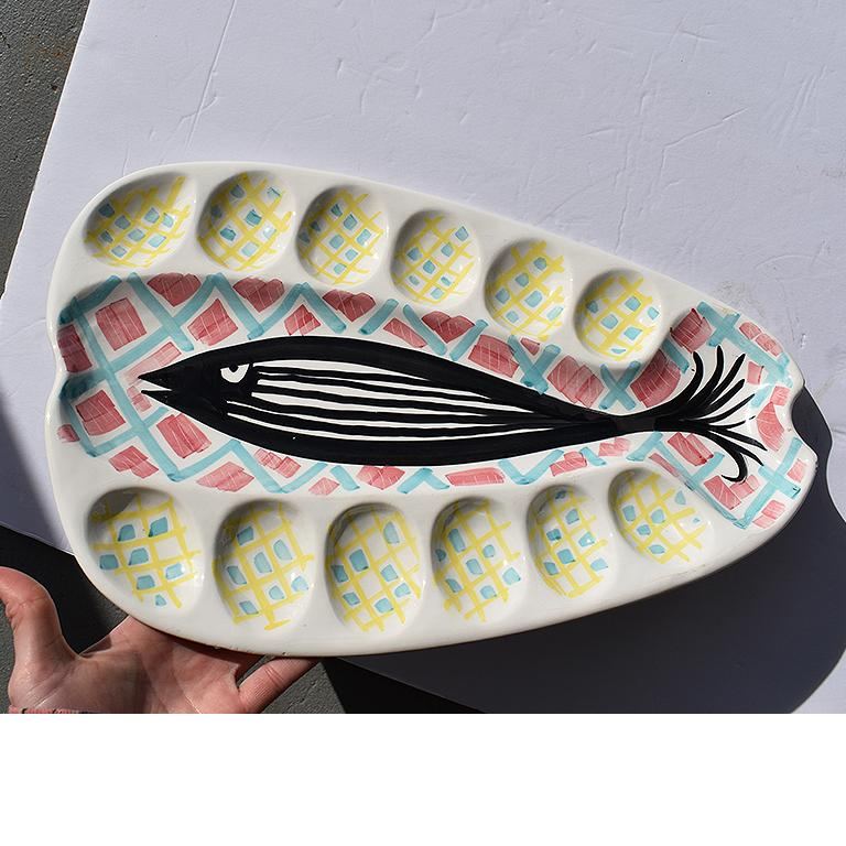 Fantastic abstract platter hand painted and decorated with a fish to the center (possibly of a Salmon?) and 12 divots for placement of oysters or eggs. A wonderful find, and a spectacular way to add fun and whimsy to a supper