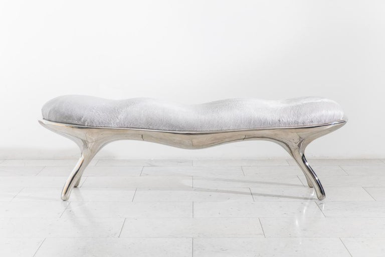 The Biche bench's muscular sculpted shape is cast in lightweight mirror-polished stainless steel. Upholstered in grey pony hair with silver metallic accents, the bench's seat is contoured to contrast the belly of the bench.
