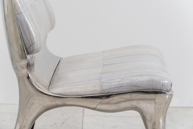 The tusk chair demonstrates Roskin's propensity for an animality in form. Created in mirror-polished stainless steel, the chair features a low seat and wide back, balancing masculine and feminine elements with forms that are active, powerful, and