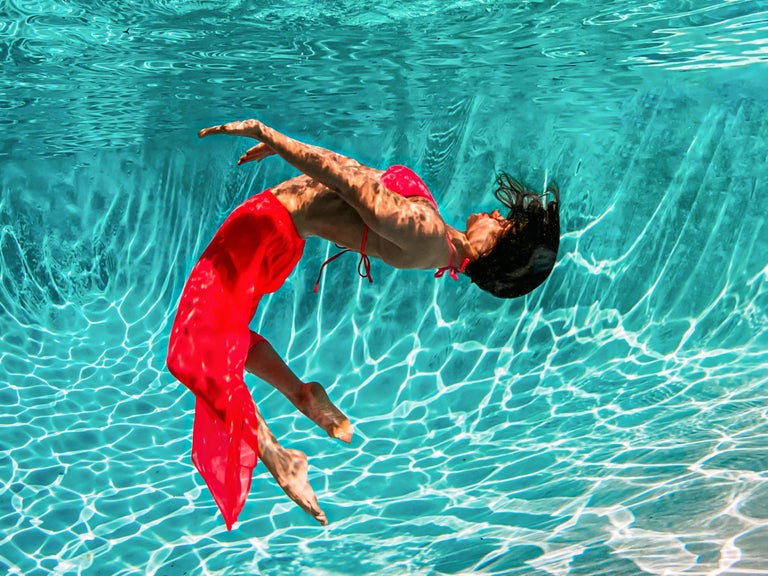 Underwater photograph of a young woman in red dress dancing underwater in a pool. A very bright photograph with plenty of sun and positivity.  Model: a Russian dancer Olga Sokolova.  Check out her performance