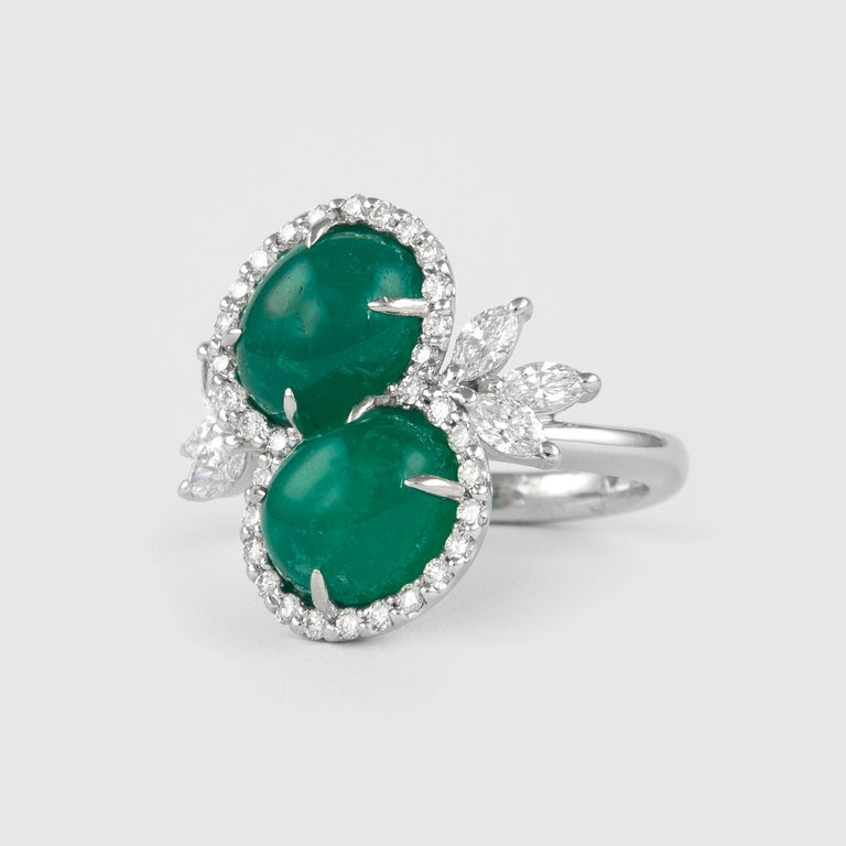 Exquisite double emerald and diamond bypass ring. By Alexander of Beverly Hills. 2 cabochon emeralds, 6.42 carats . Complemented with 0.90ct round and marquise brilliant diamonds, approximately H/I color and SI clarity. 7.32ct total gemstone weight,