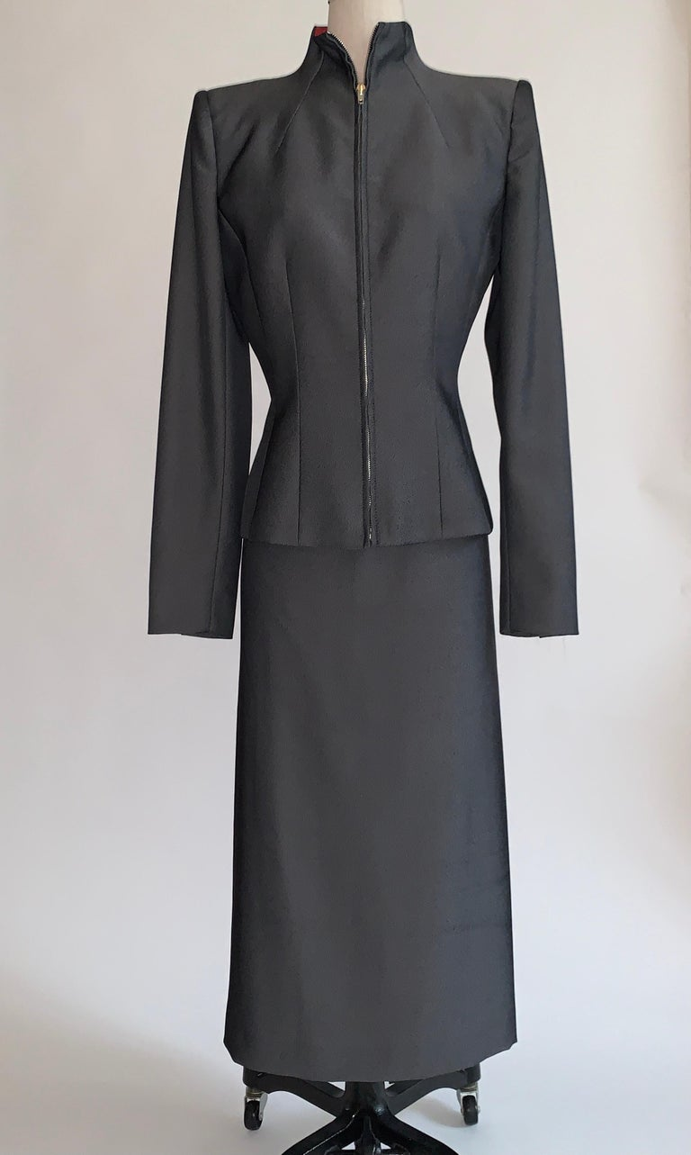 Vintage 1990s Alexander Mcqueen grey skirt suit from the 1998 Joan collection. Suit is made of a beautiful grey and black fabric with a light sheen. Amazingly tailored jacket has zippered front and light padding at shoulders for shape. Midi length