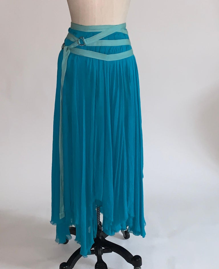 Alexander McQueen flowing blue skirt with criss cross straps at hip and asymmetrical (raw edged) distressed hem. Semi sheer, top 8 inches are lined. Sits low on the hip. Back zip and hook and eye.  Produced for the Spring 2003 Irere collection.