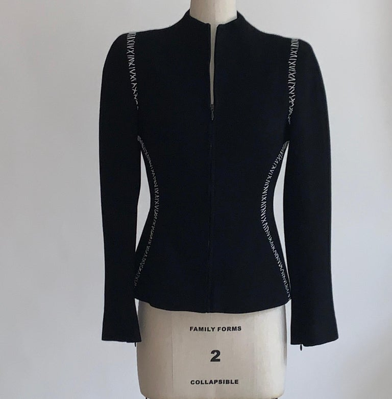 Alexander McQueen black textured wool jacket with contrasting white stitch detail. Zip front. Mid-weight padding at shoulders enhances structured silhouette, while zippers at cuff create an extra tailored sleeve. Chain at interior bottom hem