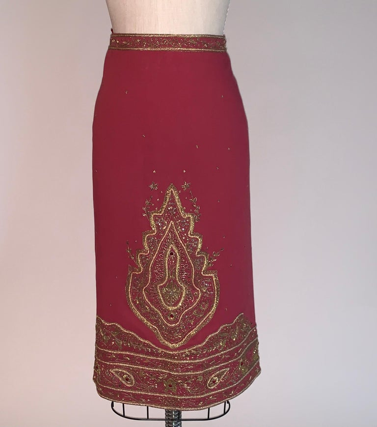 Alexander McQueen burgundy pencil skirt with intricate gold embroidered embellishment throughout. Metallic wrapped thread and cording is accented with antiqued sequins and red crystals throughout.  Back zip and hook and eye.  55% flax, 45%