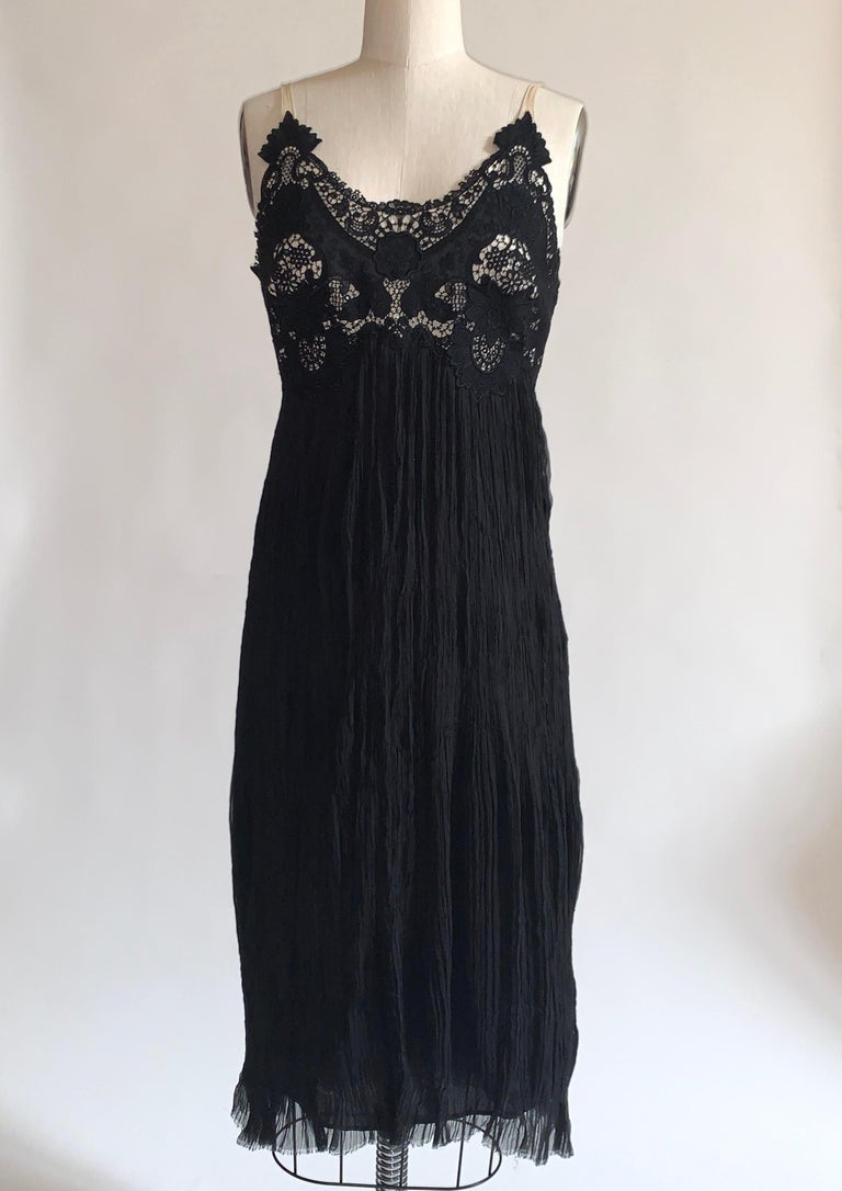 Alexander McQueen black dress featuring lace at upper bodice and skirt of crinkle pleated silk. Cream mesh straps, raw edge at hem. Back zip and hook and eye with snaps at bottom zip to conceal zipper into folds of skirt.  100% silk. Lined in 85%