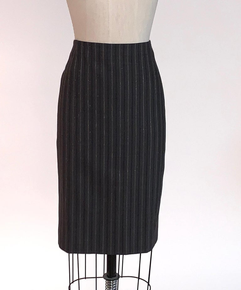 Alexander McQueen grey stripe pencil skirt with silver metallic pinstripe, circa 2007. Back zip and hook and eye.   96% wool, 2% polyamide, 2% elastane. Fully lined in 57% viscose, 43% polyester.  Made in Italy.  Size IT 42, approximate US 6, see