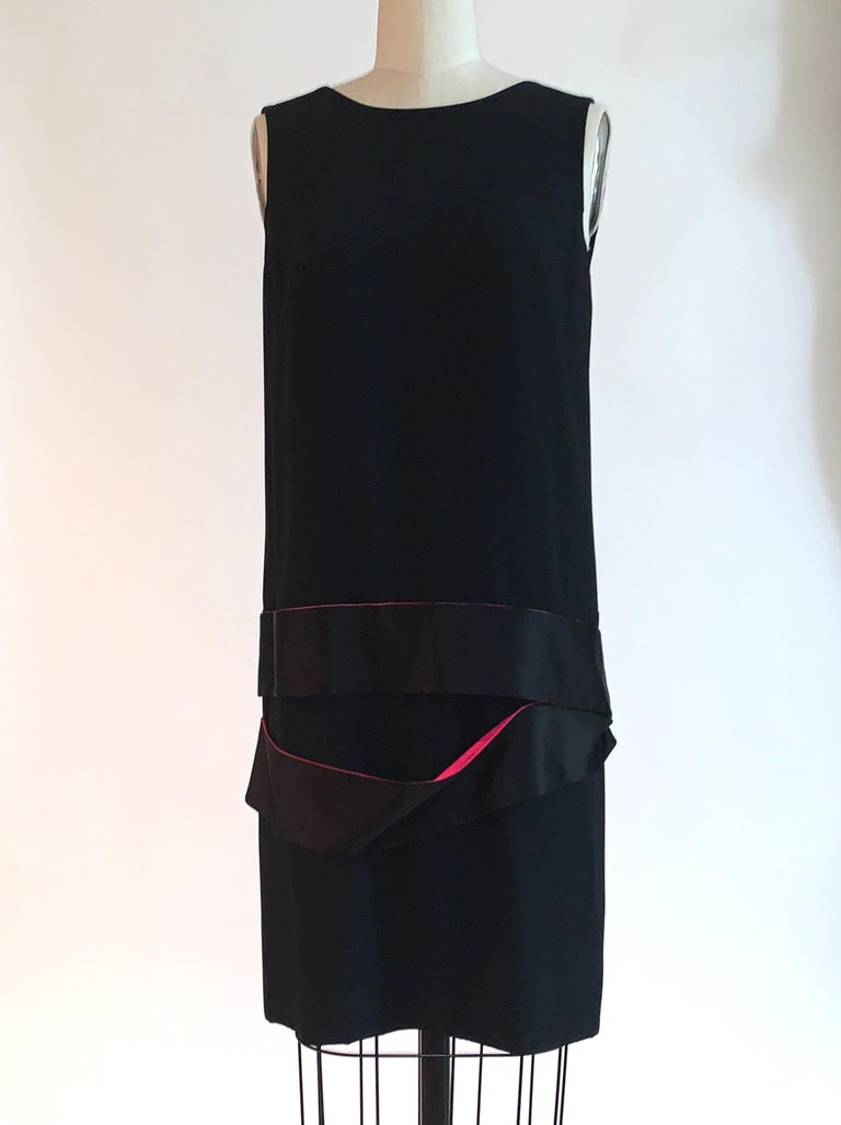 Alexander McQueen black sleeveless drop waist dress with deep v back and black and pink silk bands at dropped waist. From the 2008 collection created as a tribute to McQueen's mentor Isabella Blow. Back zip and hook and eye.   48% acetate, 48%
