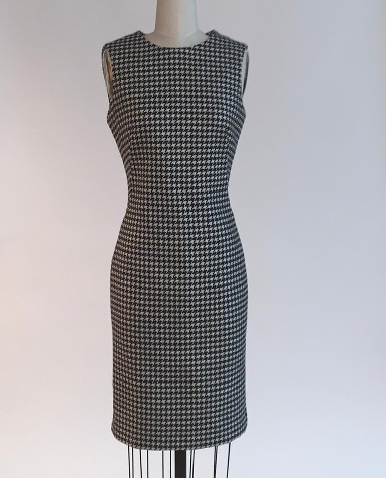 Alexander McQueen sleeveless dress in the black and white houndstooth that became so iconic from the Fall 2009 Horn of Plenty collection. Checked wool dress has boning at sides to create a beautiful tailored shape. Back zip and hook and eye.  98%