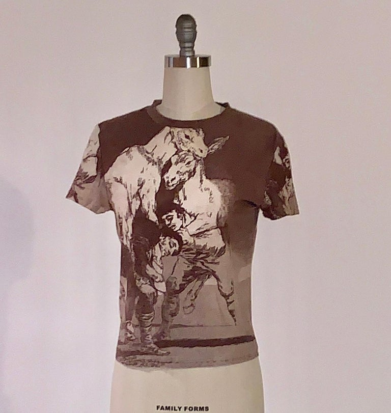 Rare Alexander McQueen 1990s short sleeve crew neck t-shirt in light brown featuring Francisco Goya's 1799 print Tu Que no Puedes (They Who Cannot) from the series Los Caprichos featuring two men straining to carry a pair of donkeys. Printed on