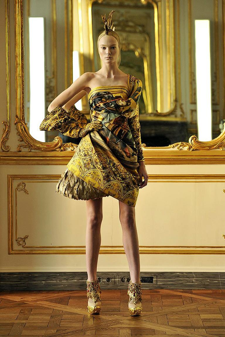 Short evening dress, the one-shouldered bodice and skirt of asymmetrically draped and swathed printed-silk with a single batwing sleeve, the skirt draped over an underskirt of gilded feathers, by Alexander McQueen, designed in London, AW 2010 look