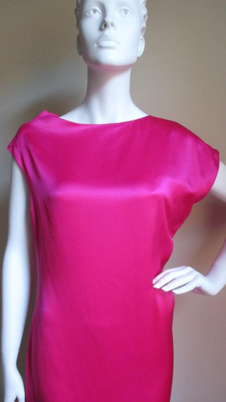 A twist on a simple sheath from Alexander McQueen in bright pink silk cut on the bias with an asymmetrical neckline and sleeves.   it has elaborate seaming, is fully lined in silk and has an invisible side zipper.   Fits size Medium.  Bust
