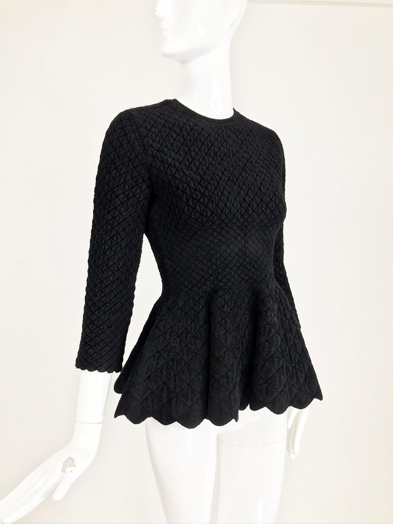 Alexander McQueen black diamond pattern stretch peplum top. This top has an amazing silhouette, the fabric feels velvety and the design done in small diamonds. The top pulls on, it has a jewel neckline, 3/4 length sleeves with scallop hem. 3 non