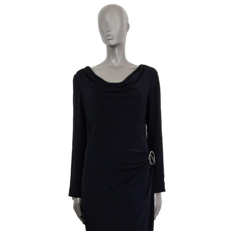 Alexander McQueen draped dress in black acetate (50%) and viscose (50%) with a cowl neck, long sleeves and a removable embossed brooch. Closes on the back with zipper. Lined in viscose (57%) and polyester (43%). Has been worn and is in excellent