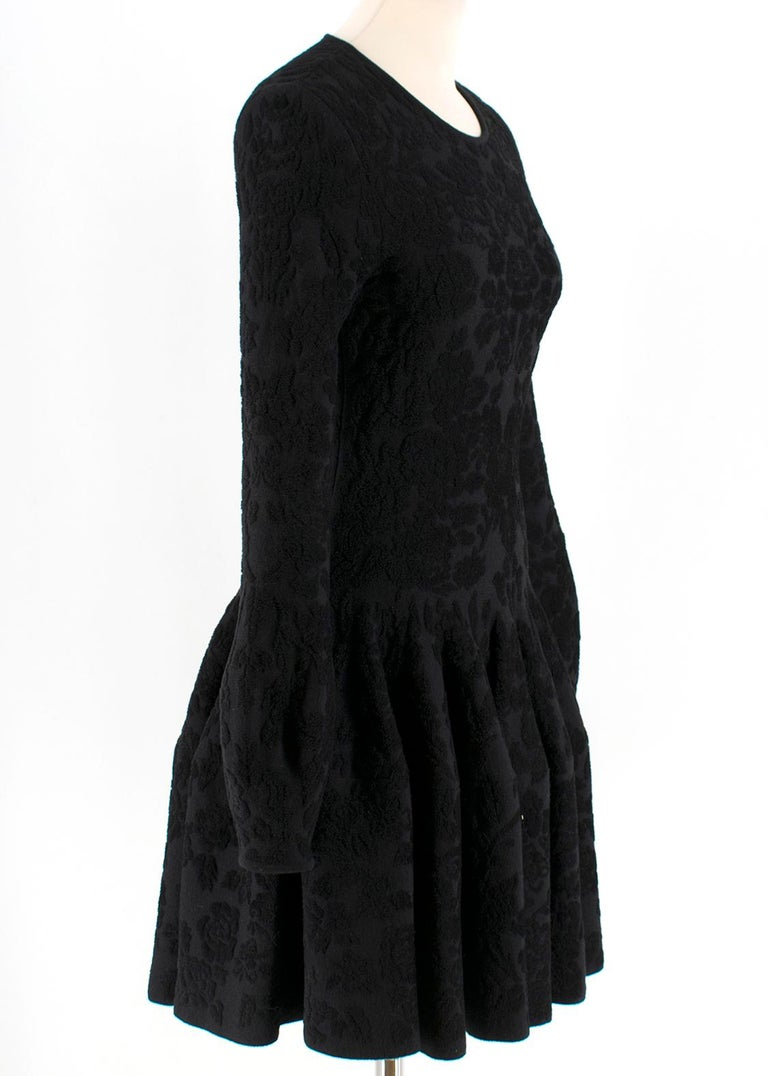 Alexander McQueen Flocked Velvet Dress   Black velvet-textured floral print Soft crew neck dress Long sleeves  Midweight material  Pleated skirt design 54% Wool, 25% Viscose, 15% Polyamide, 6% Polyester  Please note, these items are pre-owned and