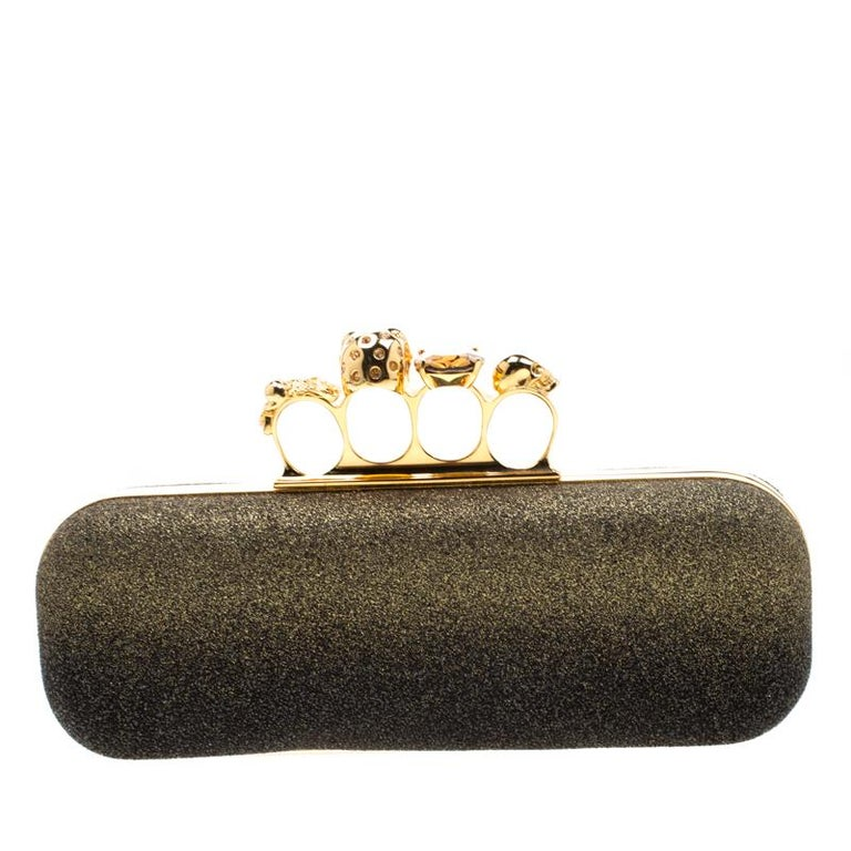 This Knuckle Clutch from Alexander McQueen exudes versatility and luxury. Crafted from black and gold ombre glitters, it features a boxy silhouette and a well-sized interior, lined with leather. This piece is complete with the brand's iconic