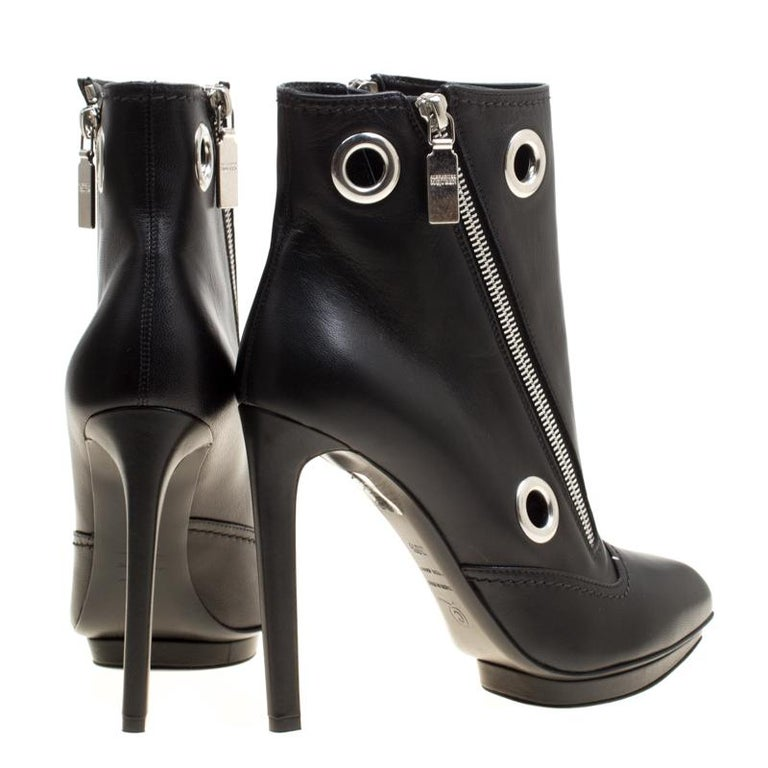 To complement your upbeat style, Alexander McQueen brings you these gorgeous ankle booties that come flowing with high-fashion. They've been crafted from leather and designed with eyelets, double zippers, and 12 cm heels.  Includes: Original