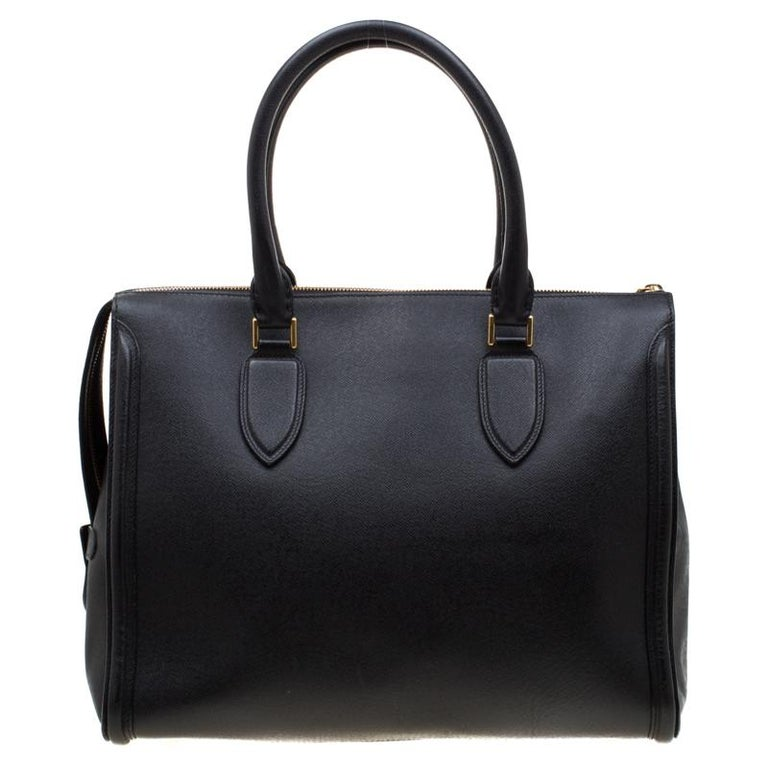 Every woman needs a bag that is pretty and functional, just like this tote from Alexander McQueen. Crafted from leather, it has a spacious canvas interior, two top handles and metal feet. This is definitely one handy bag that deserves to be