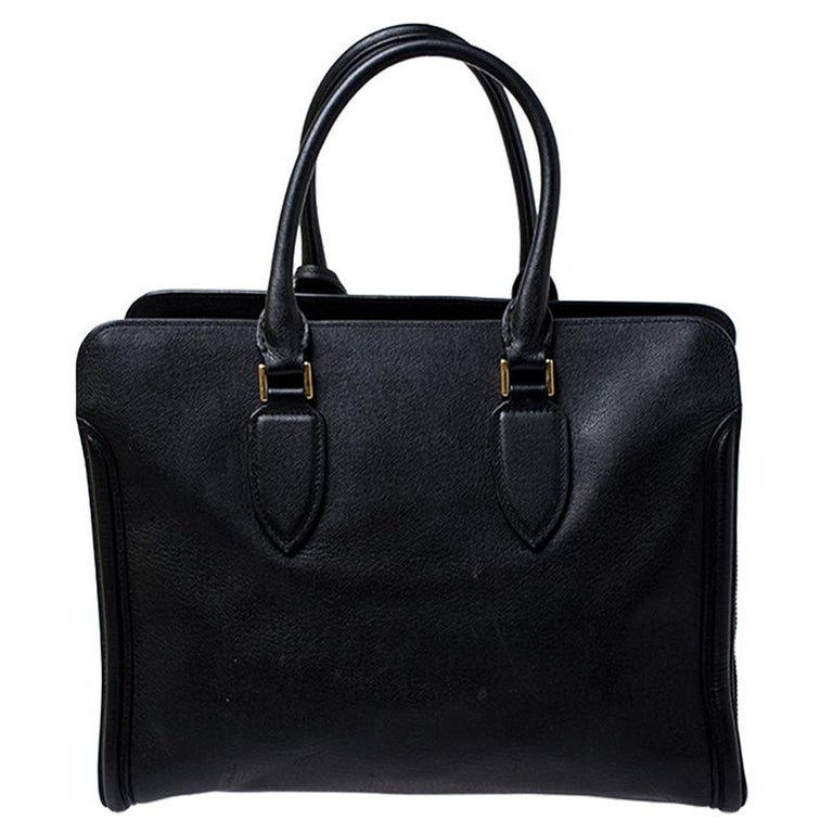 Every woman needs a bag that is lovely and functional, just like this tote from Alexander McQueen. Crafted from leather, it has a spacious canvas interior, two top handles and metal feet. This is definitely one handy bag that deserves to be