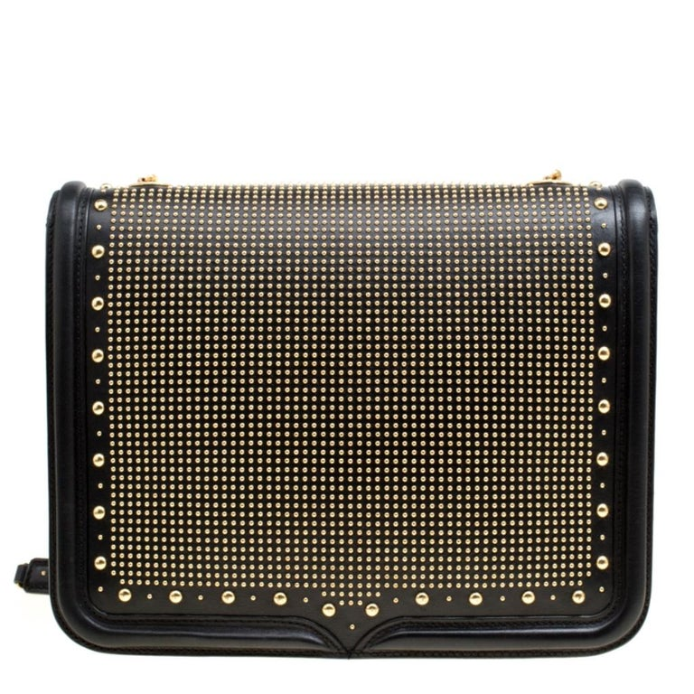 Fabulously designed, this Heroine bag from Alexander McQueen is sure to set hearts racing! It is crafted from leather and features gold-tone studs adorning the exterior. It has a tuck-in front flap closure that opens to reveal a spacious suede lined