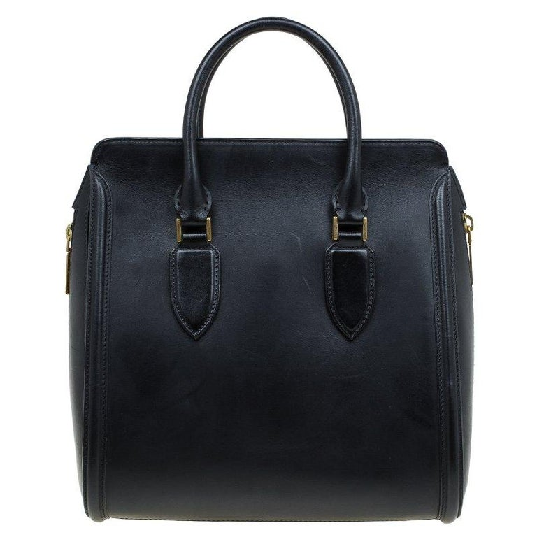 A sturdy fine leather body and double carry handles, the bag comes with a structured design and a flap closure for the main pocket. With gold-toned hardware to complement the sophisticated styling, it features a large pocket and a rigid base with