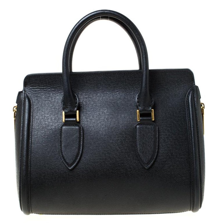 Every woman needs a bag that is pretty and functional, just like this one from Alexander McQueen. Crafted from leather, it has been styled with a flap leading to a spacious suede interior and it is held by two top handles. This is definitely one