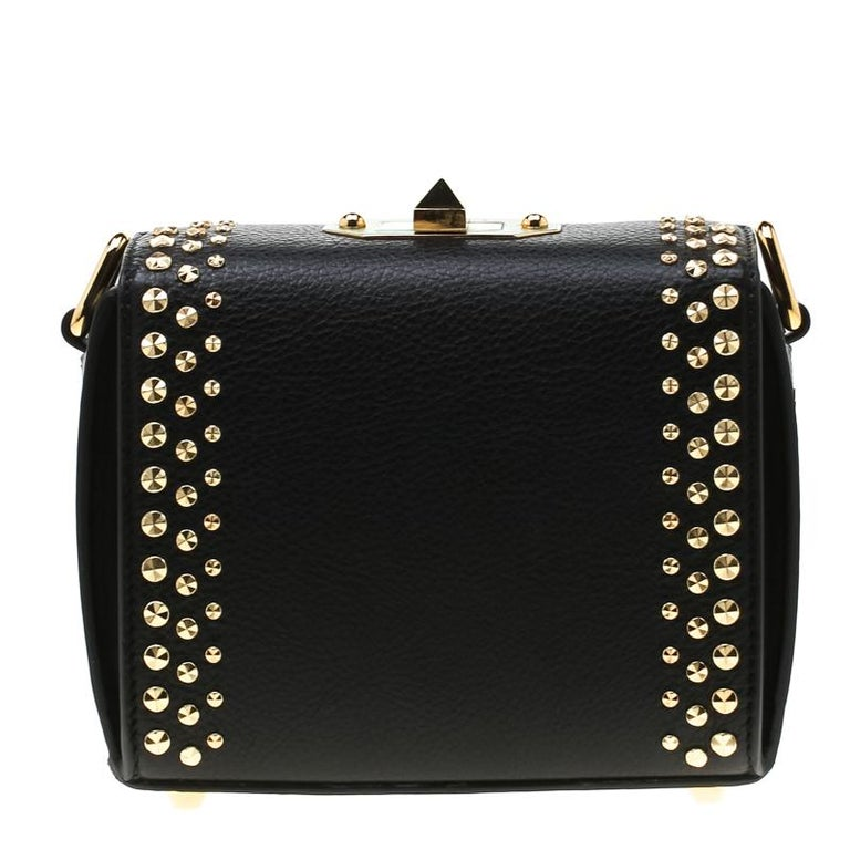 This Alexander McQueen Studded Box bag is sure to make you stand out and grab all the compliments! It is crafted from leather and features a boxy silhouette. It flaunts the brand name on the front along with gold-tone stud embellishments. It has a
